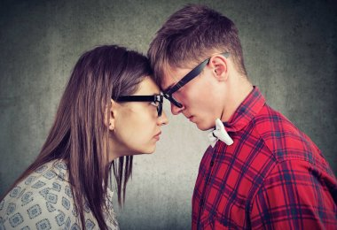 Side view of young man and woman head to head looking with hatred at each other having argument