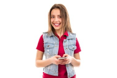 Pretty happy young woman in casual denim holding and using smartphone while smiling happily at camera on white background stock vector
