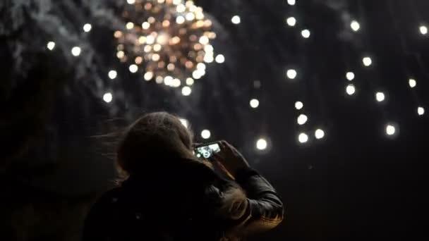 La Ragazza Prende Le Immagini Di Fuochi Dartificio Su Un Telefono Cellulare Sagoma Sullo Sfondo Del Cielo Illuminato Da Luci