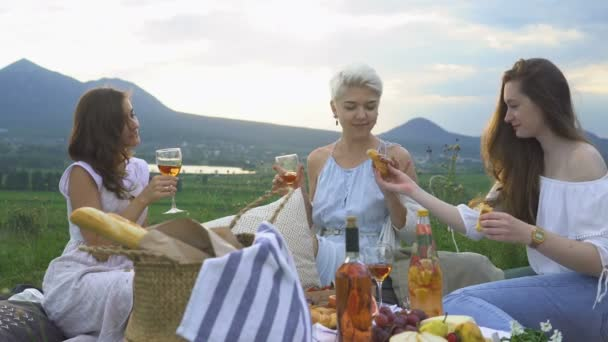 Young happy friends, laughing and drinking wine at a picnic, at sunset overlooking the mountains.