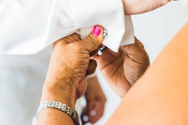 A groom putting on cuff-links as he gets dressed in his wedding
