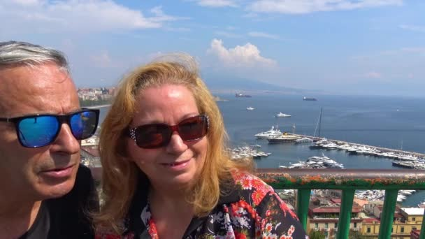 Naples, tourists look in camera with city landscape as background.