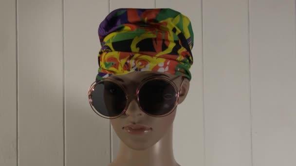Žena figurína představuje close-up pro módní video se slunečními brýlemi a barevné pásky 4K 59.94 fps