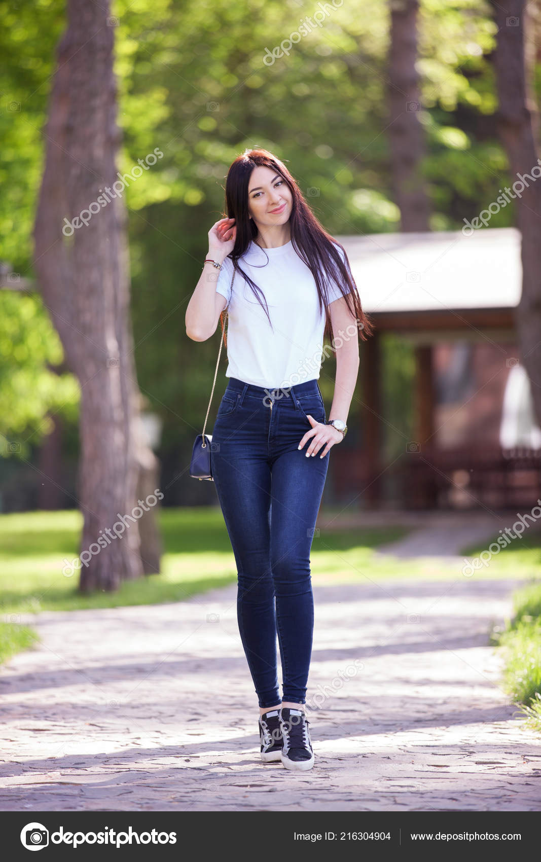 bdee211c3c8 Portrait of beautiful happy stylish woman in blue jeans and white t-shirt