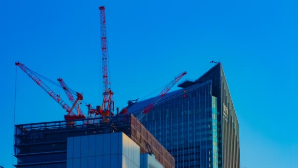 A timelapse of cranes at the under construction behind the blue sky in Tokyo