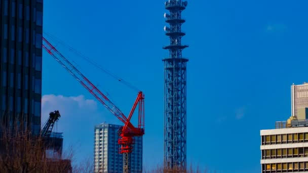 Plachý jeřáby na stavbě za modrým nebem v Tokiu