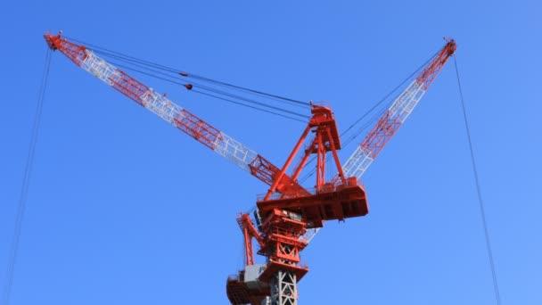 fahrende Kräne im Bau hinter dem blauen Himmel in Tokio