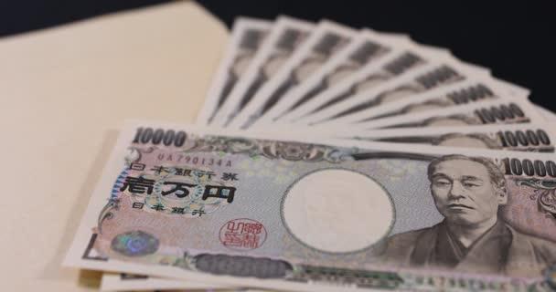 Japonská měna 100,000 jenů s obálkou na černém pozadí náklonu zaostření