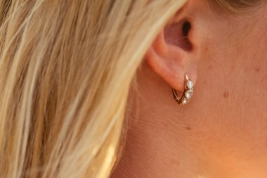 ear of a happy woman with a beautiful earring