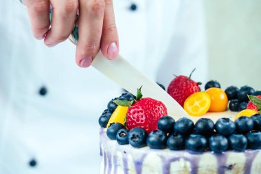 appetizing and berry wedding cake on a white background on the table. view from above . confectioner, cake, cooking. wedding and birthday cake with berries strawberries, blueberries, berries .
