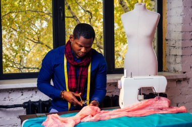 portrait of a handsome african man smiling seamstress with sewing machine.Afrio American man stylish designer working in tailor workshop mannequin,table measuring tape in room against autumn window