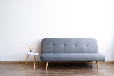Minimalistic interior design concept. Grey textile sofa in spacious room of loft style apartment with wood textured laminated flooring. Background, copy space, close up.