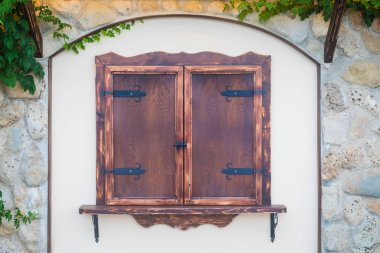 Closed Window with old brown wooden shutters