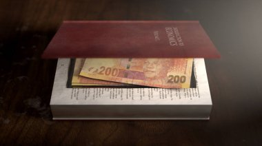A red hardback book with a cutaway area in the pages concealing a stack of rand notes on an isolated background