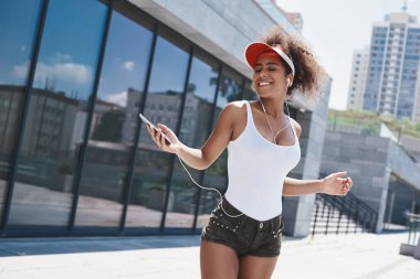 Young woman in visor and earphones free style on the street walk
