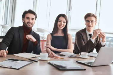 Businesspeople at office working together sitting looking camera