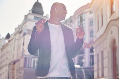Music lover. Young man wearing headphones standing on the city street listening to music closed eyes dancing smiling joyful
