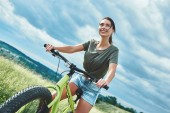 Mountain biking - woman with bike enjoy summer vacation