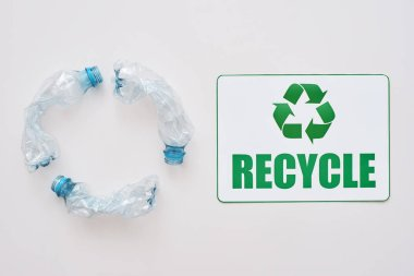 You can clean the world. Isolated recycle symbol and crumple plastic bottles