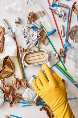 Clean the world. Hand in orange glove under the trash
