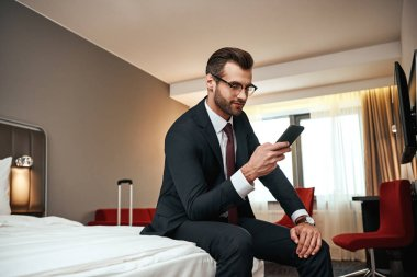 Relax after long business trip. Businessman in business suit sitting with smartphone on bed at hotel room and chatting with a friend stock vector
