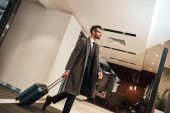 Happy young man with travel bag walking inside hotel