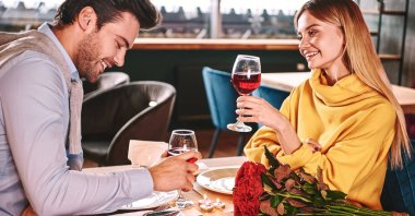 Cherful talking in restaurant. Couple holding red wine in glasses in restaurant. Red roses and candles are lying on the table near the red wine. Young woman in mustard sweater looks at her boyfriend stock vector