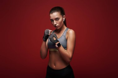 New champion. Young sportswoman standing over red background is ready to exercise