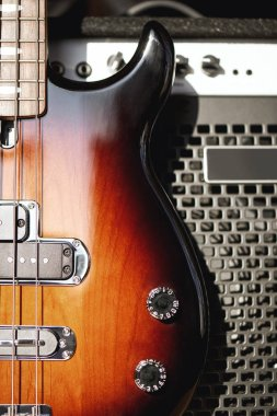 Playing guitar...Close up photo of a brown electric guitar with volume and tone control knobs and amplifier