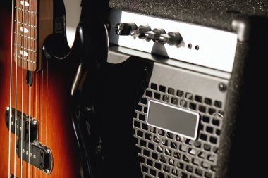 Beautiful and perfect polished electric guitar with amplifier standing in audio recording studio. Music theme