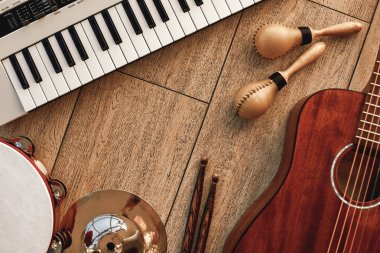 Creating a melody...Top view of musical instruments set: synthesizer, electronic guitar, wooden drum sticks, golden cymbal, drums, gold maracas and tambourine lying on wooden background.