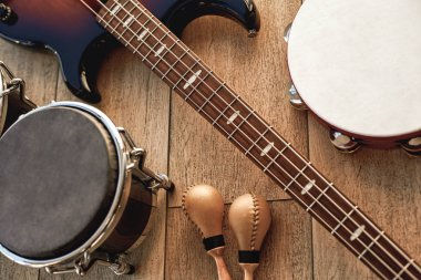 At the rehearsal in the studio. Top view of musical instruments set: brown electric guitar, drums, gold maracas and tambourine lying on wooden background