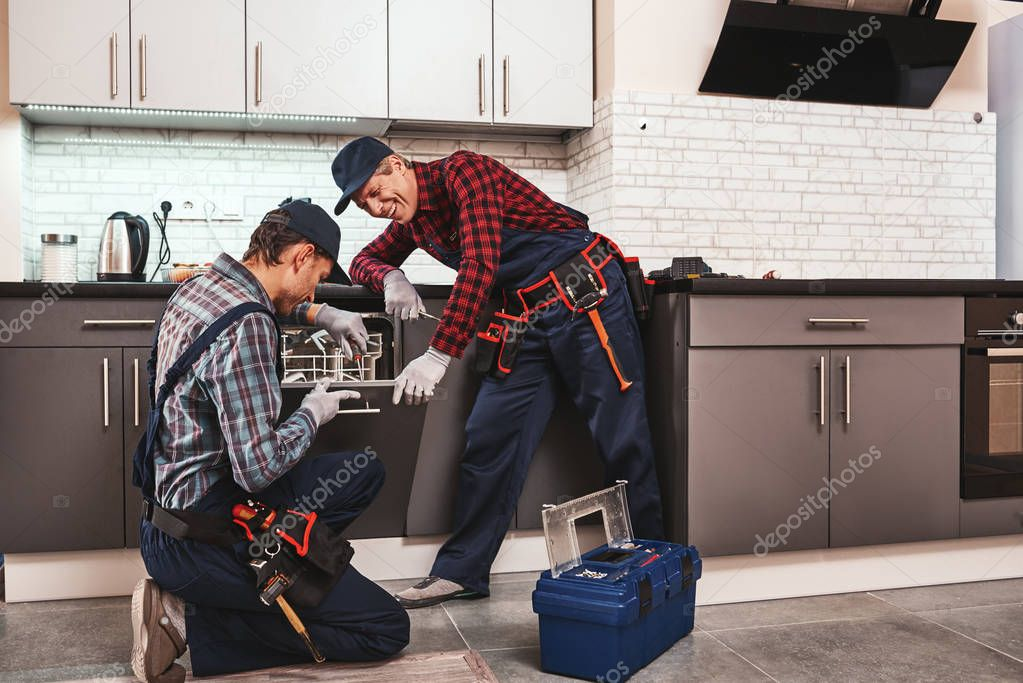 Take a pleasure from success. Two men technician sitting near dishwasher
