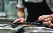 Kreativní vaření. Oříznout obrázek z rukou šéfkuchaře, obloha těstoviny carbonara v kuchyni restaurace.