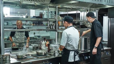 Cooking process. Professional team of chef and two young assistant preparing food in a restaurant kitchen