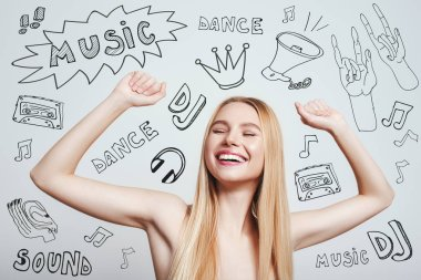 DJ party. Happy young blonde woman with naked shoulders smiling with raised hands while standing against grey background with music theme doodles