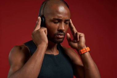 Music is my motivation. Portrait of handsome afro american man in headphones keeping eyes closed while standing against red background