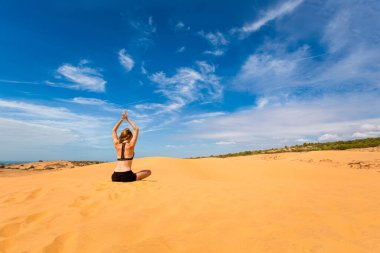 Beautiful caucasian girl meditating on Red sand dunes in Mui Ne, Phan Tiet area in Vietnam. Landscape with blue sky during sunny day.