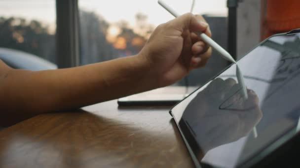 Die Hand zeichnet auf dem Tablet im Wohnzimmer