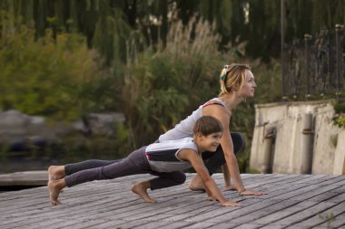 Mother and son exercising yoga  pose in nature