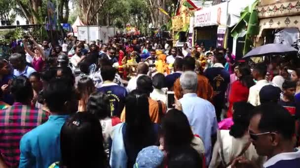 Golden kavadi carried at shoulder follow by family members.