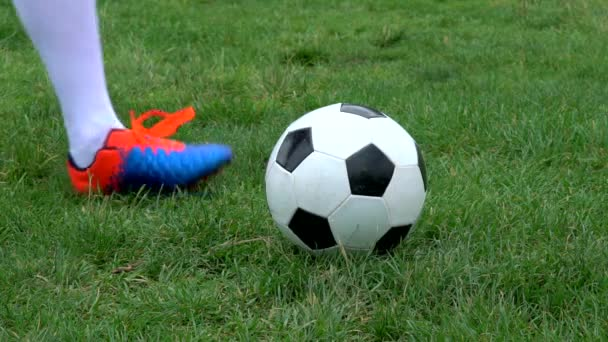 Football player hits the ball in a slow motion close-up