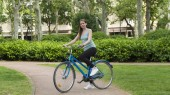 Girl rides bicycle in a city park