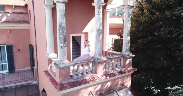 die junge Frau winkt mit der Hand auf dem Balkon einer alten italienischen Villa