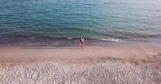 Piombino, Toskánsko, Itálie. Mladý dospělý pár podél pobřeží při západu slunce