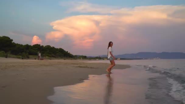 Piombino, Toskánsko, Itálie. Veselá dívka chodí a jezdí na západ slunce na pláži