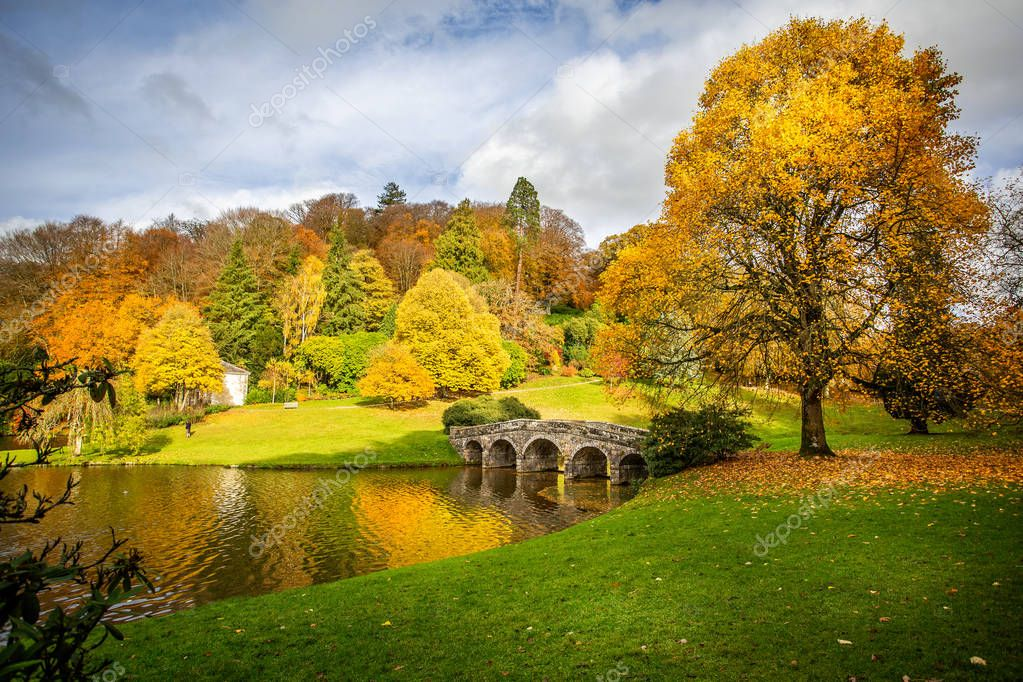 Autumn landscape with golden yellow, orange and green trees in Stourhead, Wiltshire, UK on 8 November 2018