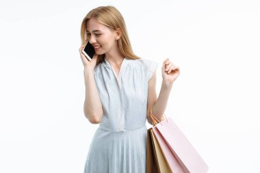 Young beautiful girl posing with phone, with shopping, on white background, with gift bags, talking on phone and smiling,
