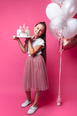 girl with a cake for a birthday, in the Studio on a pink background