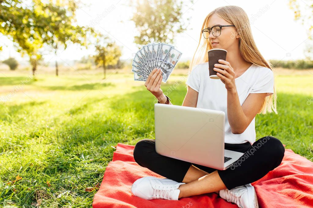 business lady with glasses, who is in the Park sitting on a blanket, holding money in her hands, and drinking coffee, close-up image of dollars